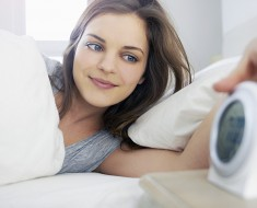 young woman with alarm clock in bed